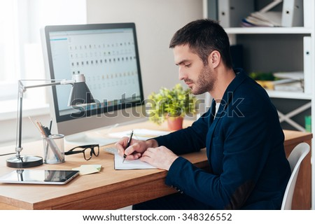 Concentrated on work. Side view of confident young man writing something in his notebook while sitting at his working place in office - stock photo