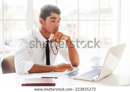 Concentrated on work.  Side view of thoughtful Afro-American young man in formalwear looking at laptop and holding hand with glasses on chin while sitting at his working place - stock photo