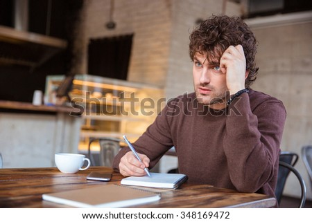 Concentrated pensive handsome curly pensive young man in brown sweetshirt writing in notebook sitting in cafe and drinking tea - stock photo