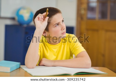 Concentrated pupil working at his desk in a classroom in school - stock photo