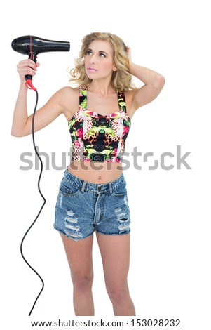 Concentrated retro blonde model using a hair dryer on white background - stock photo