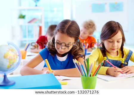 Concentrated school children being occupied with a task - stock photo