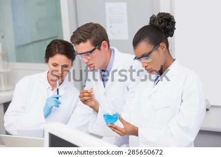 Concentrated scientists working together in laboratory - stock photo