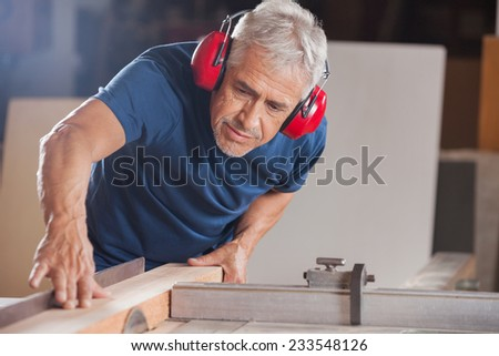 Concentrated senior male carpenter cutting wood with tablesaw in workshop - stock photo