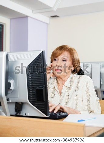 Concentrated Senior Student Using Computer In Classroom - stock photo