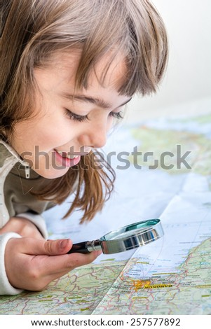 Concentrated seven year old girl examining the map with a magnifying glass - stock photo