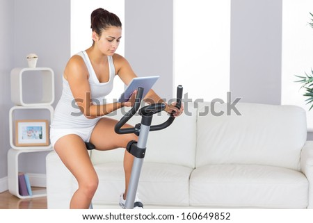 Concentrated slender woman training on an exercise bike while using her tablet in her living room - stock photo
