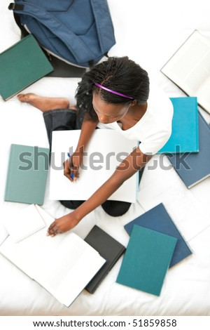 Concentrated teen girl studying sitting on her bed at home - stock photo