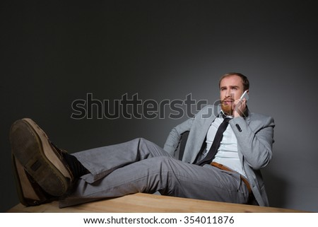 Concentrated thoughtful business man in grey suit talking on mobile phone over grey background