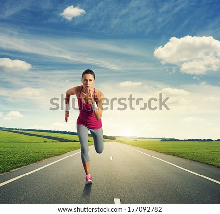 concentrated woman running on the road - stock photo