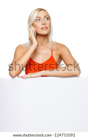 Concentrated woman standing behind and leaning on a white blank billboard / placard, talking on cellphone, looking away, over white background - stock photo