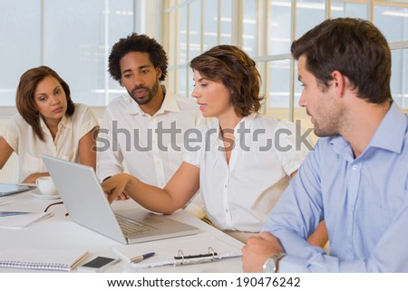 Concentrated young business people using laptop in meeting at office desk