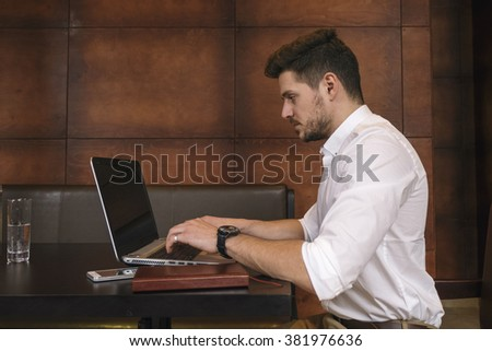 Concentrated young businessman sitting at workplace while typing on laptop. Brown wooden wall on background
