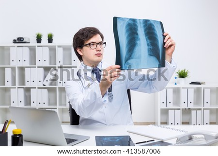 Concentrated young doctor sitting at his office and attentively examining an x-ray - stock photo