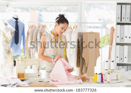 Concentrated young female fashion designer at work in a studio - stock photo