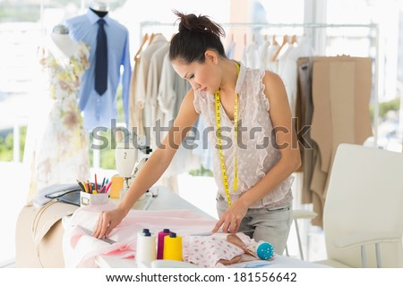 Concentrated young female fashion designer working on fabrics in the studio - stock photo