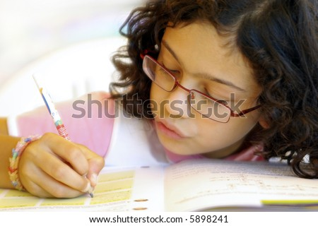 Concentrated young girl doing her school home-work. - stock photo