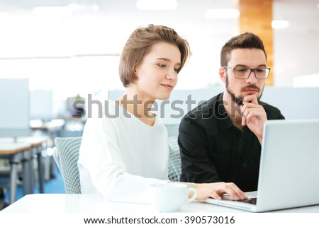 Concentrated young man and woman sitting and discussing new project using laptop in office - stock photo