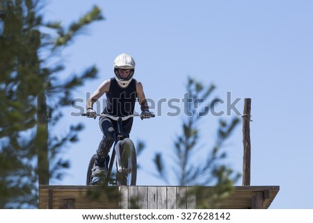 concentrated young man BMX rider is ready to jump on a wooden ramp on a BMX session in the mountain - focus on the face - stock photo