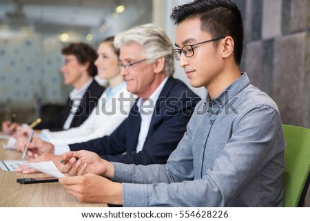 Concentrated young manager examining document