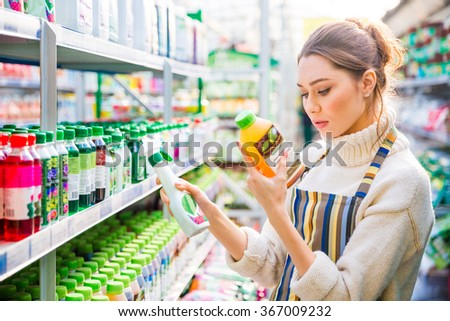 Concentrated young woman choosing agricultural chemicals for flowers and plants in store