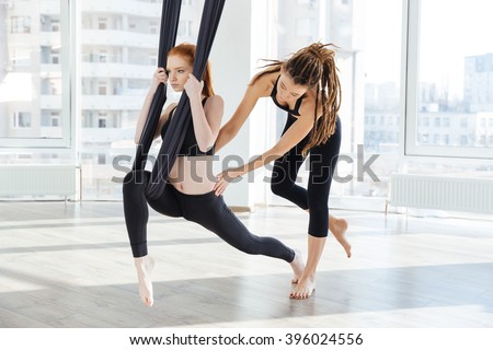 Concentrated young woman doing antigravity yoga using hammock with help of personal trainer - stock photo