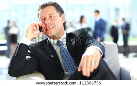 Concentrating businessman on call, coworkers talkling in background - stock photo