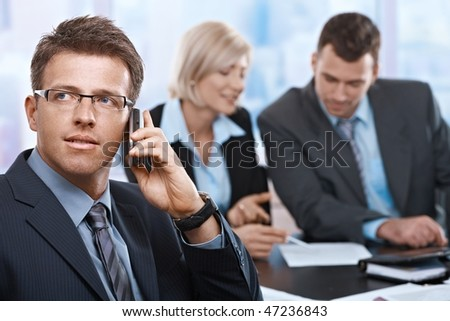 Concentrating businessman on call, coworkers talkling in background.