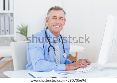 Concentrating doctor using computer in medical office - stock photo