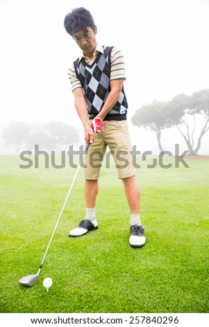 Concentrating golfer lining up his shot at the golf course - stock photo