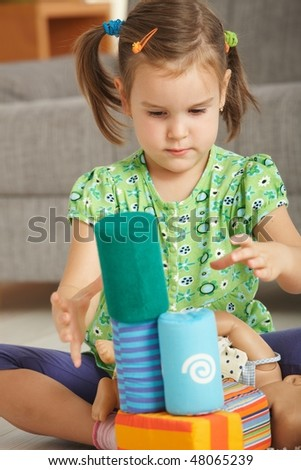 Concentrating little girl (3-4 years) playing with toy blocks at home. - stock photo