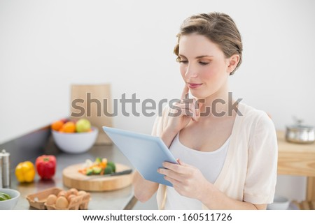 Concentrating young woman using her tablet standing in her kitchen at home - stock photo