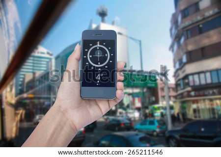 Concept a Hand Holding a Compass on smart phone in downtown background - stock photo