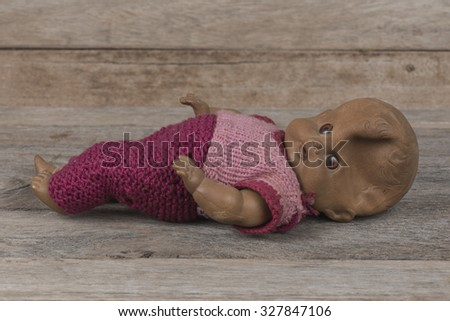 Concept: Abandoned Person. Close up an old broken doll at street. Grunge processing image in vintage style with special grain and texture for more dramatic view  - stock photo