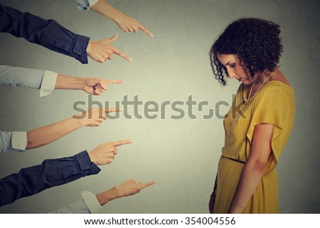 Concept accusation guilty person girl. Side profile sad upset woman looking down many fingers pointing at her back isolated grey office wall background. Negative human face expression emotion feeling  - stock photo