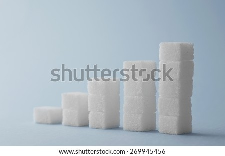 Concept: Ascending stacks of sugar cubes over blue background. This in a concept for high risk of diabetes or other diseases caused by excessive consumption of sugar