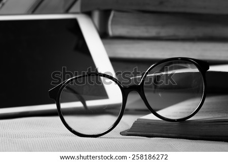 Concept book and tablet PC and eyeglasses on table.