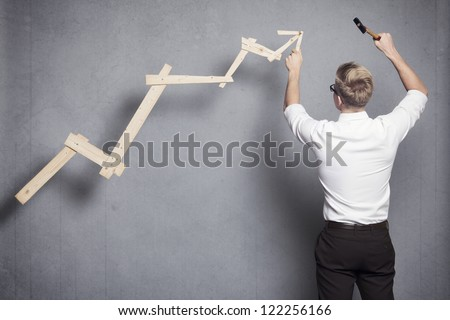 Concept: Building your own career or business. Young businessman installing upward arrow on floating business graph with positive trend, isolated on grey background. - stock photo