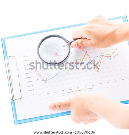 Concept business by magnifier and graphs go to target on clipboard. - stock photo