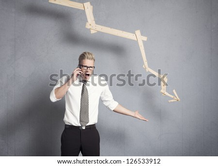 Concept: Business crisis. Enraged young businessman shouting on the phone in front of business graph with negative trend, isolated on grey background. - stock photo