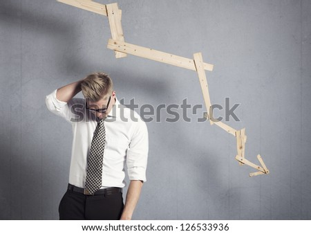 Concept: Business failure. Young worried businessman in front of business graph with negative trend, isolated on grey background. - stock photo