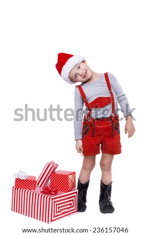 Concept: Christmas in childhood. Kid in red costume of dwarf with gifts. Studio portrait isolated over white background