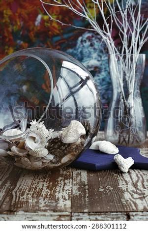 concept composition of white colored branches on the artbackground with glass samll aquarium full with seashells - stock photo