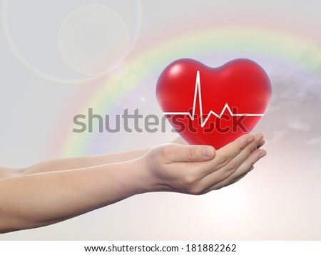 Concept conceptual 3D red human heart sign or symbol held in human man or woman hands, rainbow sky background, metaphor to health, care, medicine, protect, life, medical, pulse, healthcare cardiology