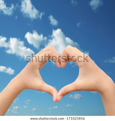 Concept conceptual human male or man and woman hands in love, Valentines shape or symbol of heart over blue sky background, metaphor to romance, romantic, wedding, honeymoon, holiday, vacation couple