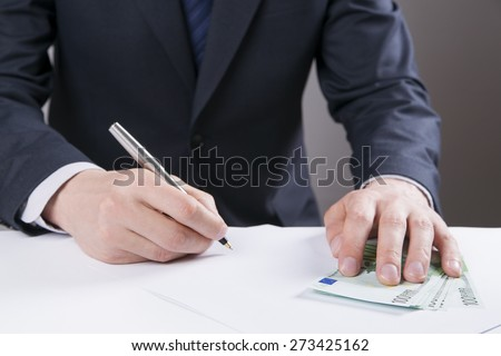 Concept - corruption. Giving a bribe. Money in hand. Sign the document. - stock photo
