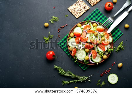 Concept diet food. Salad of fresh vegetables such as lettuce, purple onion, olives, cucumbers and tomatoes on a dark background. Vegetarian healthy dish - stock photo