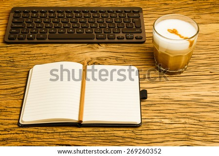 Concept empty notebook with pencil and keyboard, start of the day. Coffee on oak desk. - stock photo