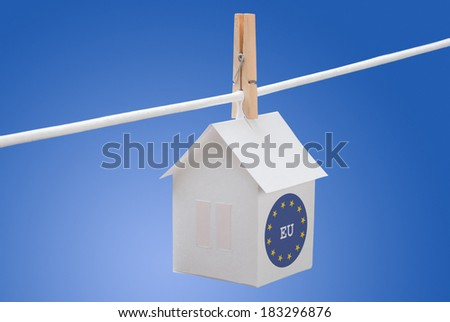 concept - EU logo flag painted on a paper house hanging on a rope - stock photo