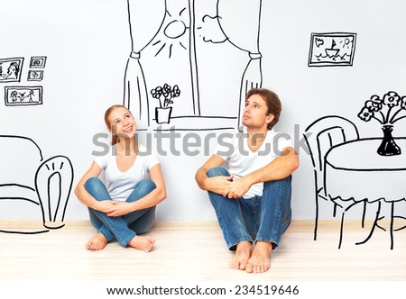 Concept family: Happy couple in the new apartment dream and plan interior - stock photo